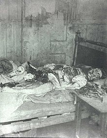 Black and white photograph of an eviscerated human body lying on a bed. The face is mutilated.